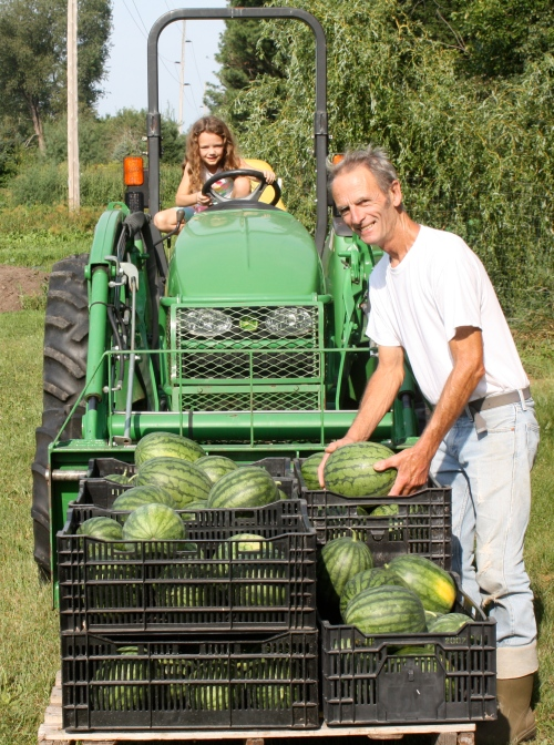 Maeve and Scott bringing the melon harvest in from the field.
