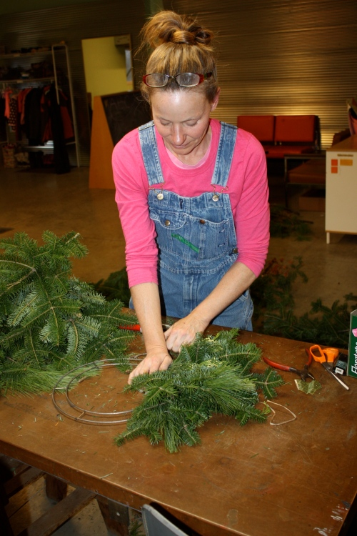 Making holiday evergreen wreaths.